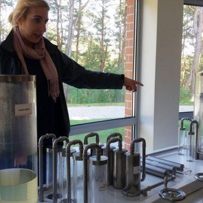 Pani przewodnik przy interaktywnej wystawie prezentujacej proces uzdatniania wody